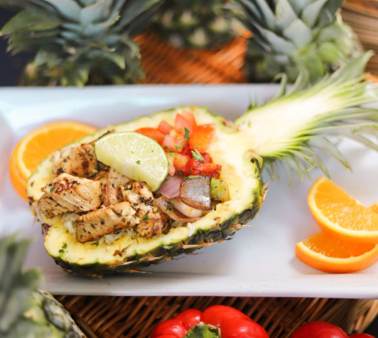 pineapple bowl filled with chicken, tomatoes, peppers and onions