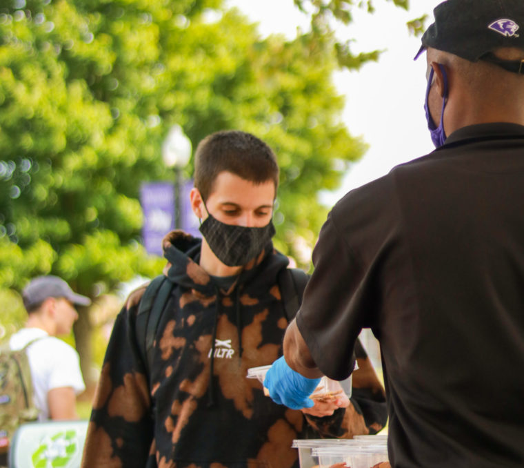 Associate handing out food from a campus kiosk to a student